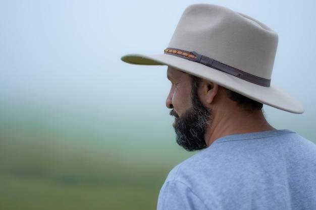 안개 낀 시골에서 휴가를 보내는 모자와 수염을 기른 히스패닉 남자