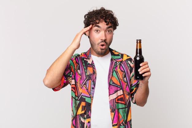 幸せそうに見え、驚き、驚き、笑顔で、驚くべき信じられないほどの良いニュースを実現するビールを持ったヒスパニック系の男性