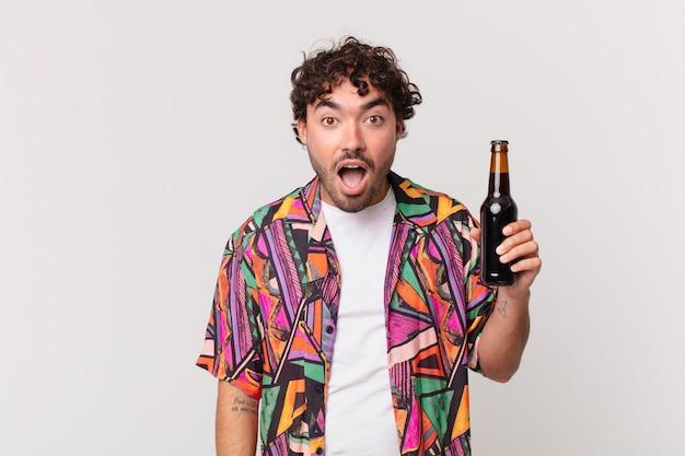 非常にショックを受けた、または驚いたように見えるビールを持ったヒスパニック系の男性が、すごいことを言って口を開けて見つめています