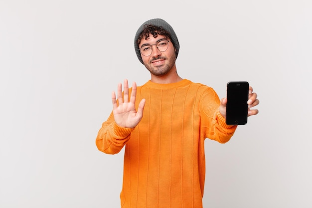 Hispanic man with a cell smiling happily and cheerfully, waving hand, welcoming and greeting you, or saying goodbye