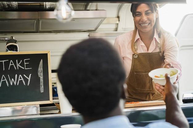 히스패닉계 성숙한 여성이 푸드트럭 안에서 음식을 가져간다 - 여성의 얼굴에 초점을 맞춘다