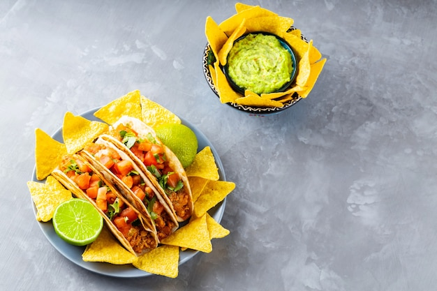 Испаноязычная мексиканская кухня. тарелка с тако и чипсами из тортильи на сером фоне. мексиканские тако, чипсы начо и соус гуакамоле. скопируйте пространство. вид сверху