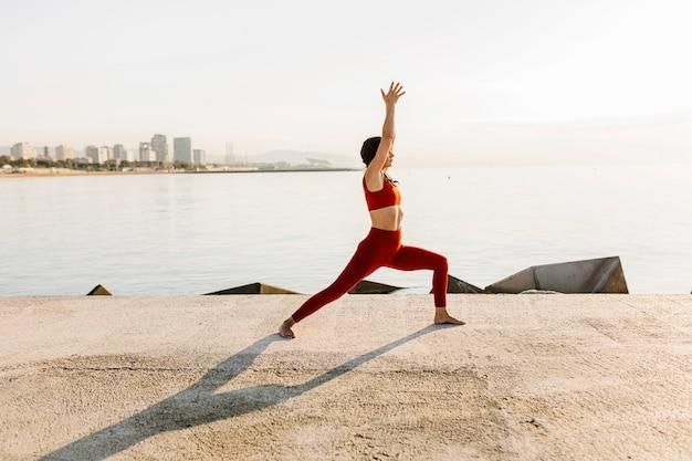 ヨガをして海で瞑想しているヒスパニック系の中間成人女性-ビーチの夕日で瞑想している戦士のヨガのポーズ(virabhadrasana)を練習しているフィットネス女性-ウェルネスとヘルスケアのライフスタイルの概念