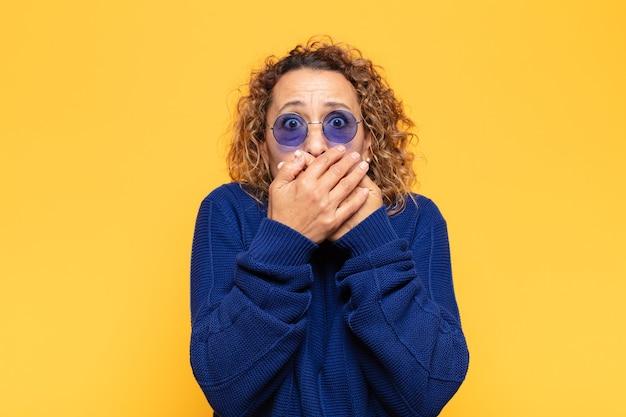 Латиноамериканка среднего возраста закрывает рот руками с шокированным, удивленным выражением лица, хранит секрет или говорит: ой
