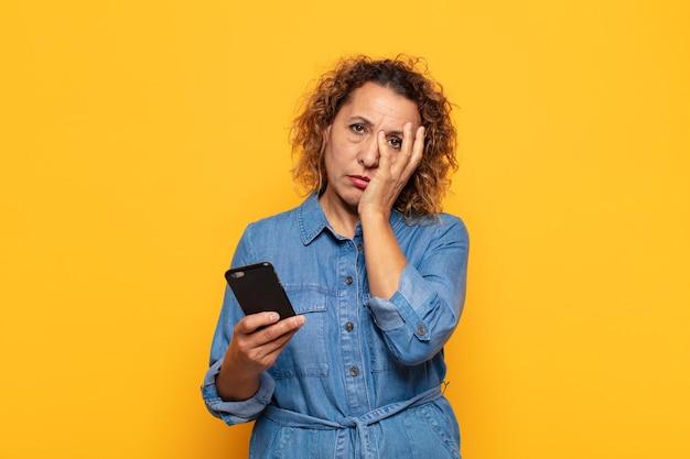 Латиноамериканская женщина среднего возраста чувствует скуку, разочарование и сонливость после утомительной, скучной и утомительной работы, держась за лицо рукой