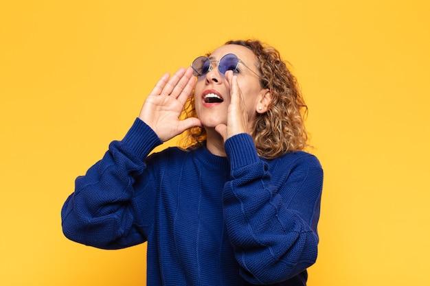 Латиноамериканская женщина среднего возраста чувствует себя счастливой, взволнованной и позитивной, громко кричит, прижав руки ко рту, выкрикивая