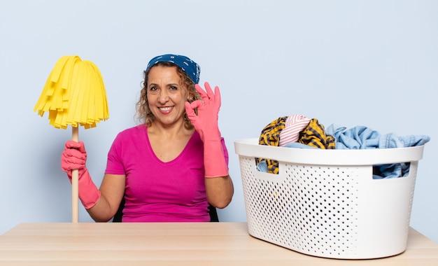 Латиноамериканская женщина среднего возраста чувствует себя счастливой, расслабленной и удовлетворенной, демонстрирует одобрение жестом ок, улыбается