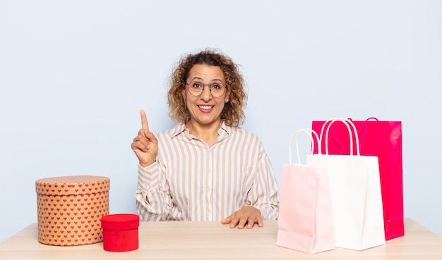 Hispanic middle age woman feeling like a happy and excited genius after realizing an idea, cheerfully raising finger, eureka!