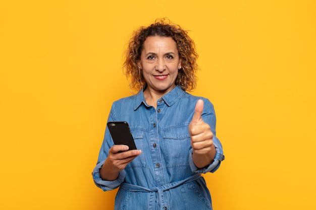 Латиноамериканская женщина среднего возраста чувствует себя гордой, беззаботной, уверенной и счастливой, позитивно улыбается и показывает палец вверх