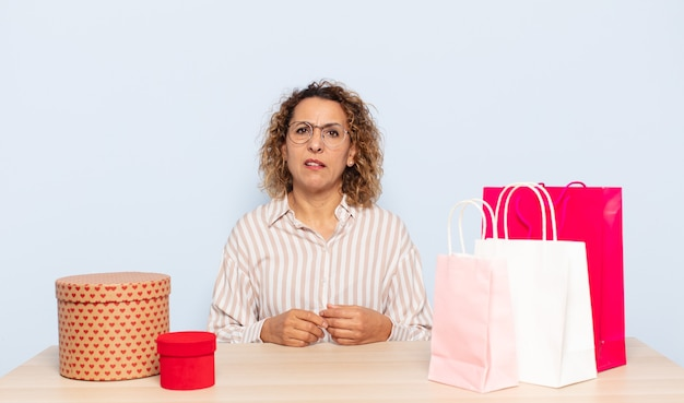 Hispanic middle age woman feeling puzzled and confused, with a dumb, stunned expression looking at something unexpected
