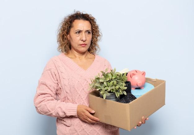 Женщина среднего возраста латиноамериканского происхождения, грустная, расстроенная или злая, смотрит в сторону с негативным отношением, хмурясь в знак несогласия