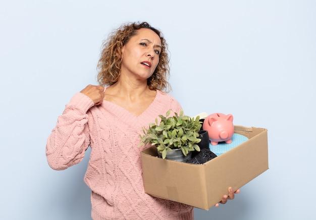 Латиноамериканская женщина среднего возраста чувствует стресс, тревогу, усталость и разочарование, тянет рубашку за шею, выглядит расстроенной проблемой