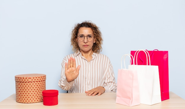 Hispanic middle age woman looking serious, stern, displeased and angry showing open palm making stop gesture