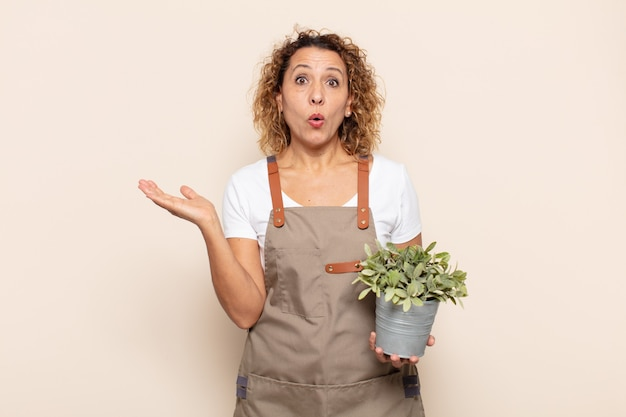 Hispanic middle age woman looking surprised and shocked, with jaw dropped holding an object with an open hand on the side