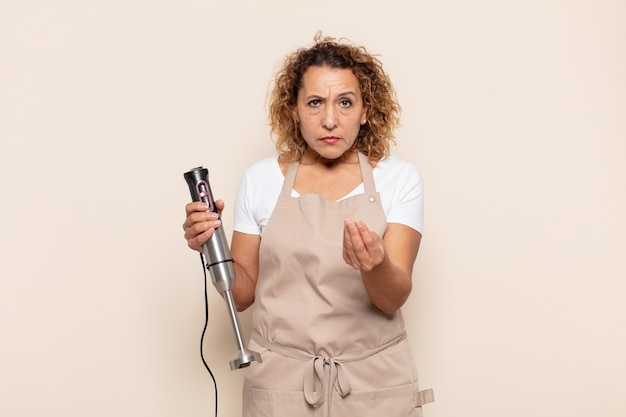 Hispanic middle age woman making capice or money gesture, telling you to pay your debts!