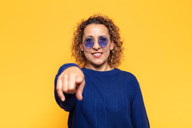 Латиноамериканская женщина среднего возраста с довольной, уверенной, дружелюбной улыбкой, указывая в камеру, выбирает вас