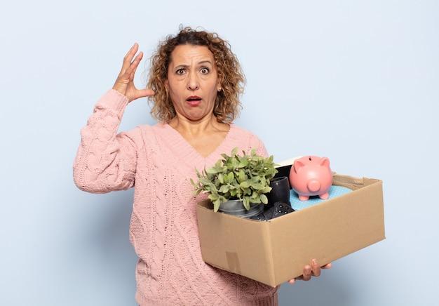Латиноамериканская женщина среднего возраста кричит с поднятыми руками, чувствуя ярость, разочарование, стресс и расстройство