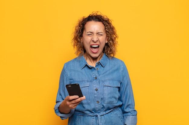 Латиноамериканка среднего возраста агрессивно кричит, выглядит очень сердитой, расстроенной, возмущенной или раздраженной, кричит