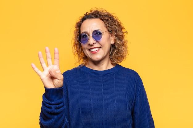 히스패닉 중년 여성 미소하고 친절하게보고, 앞으로 손으로 4 번 또는 4 번을 보여주는 카운트 다운