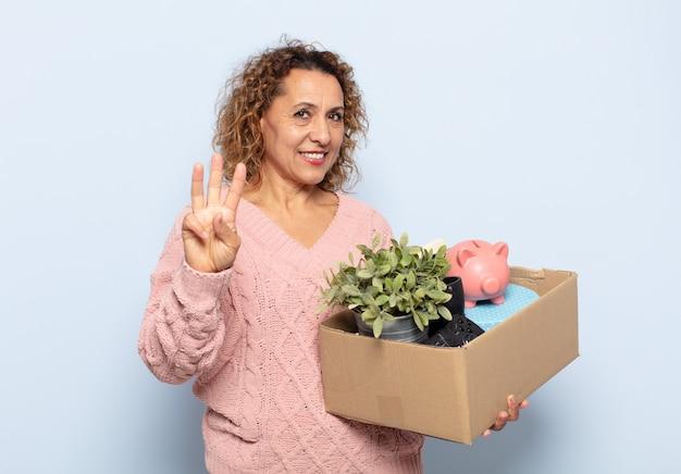 히스패닉 중년 여성이 미소하고 친절하게보고, 앞으로 손으로 세 번째 또는 세 번째를 보여주는 카운트 다운