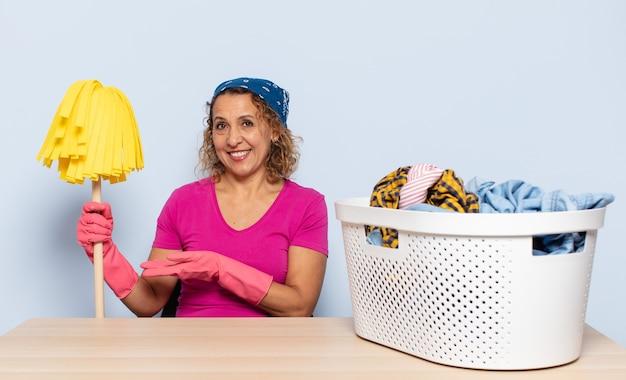유쾌하게 웃고, 행복감을 느끼고 손바닥으로 복사 공간에 개념을 보여주는 히스패닉 중년 여성