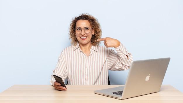 Латиноамериканская женщина среднего возраста уверенно улыбается, указывая на собственную широкую улыбку, позитивное, расслабленное, удовлетворенное отношение