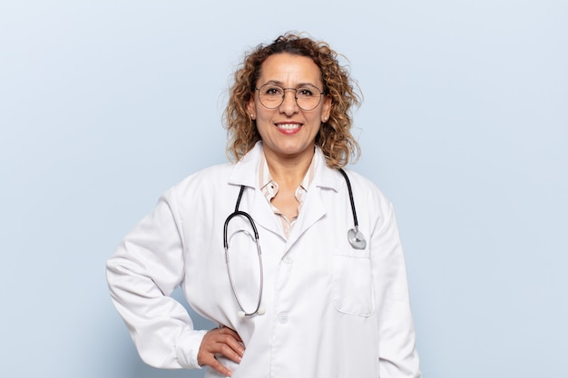 Hispanic middle age woman smiling happily with a hand on hip and confident, positive, proud and friendly attitude