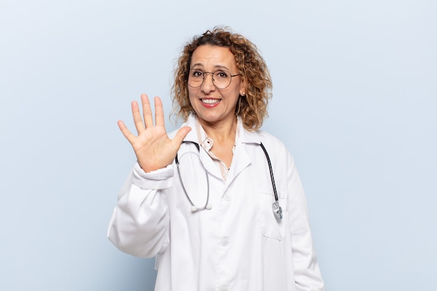 Hispanic middle age woman smiling and looking friendly, showing number five or fifth with hand forward, counting down