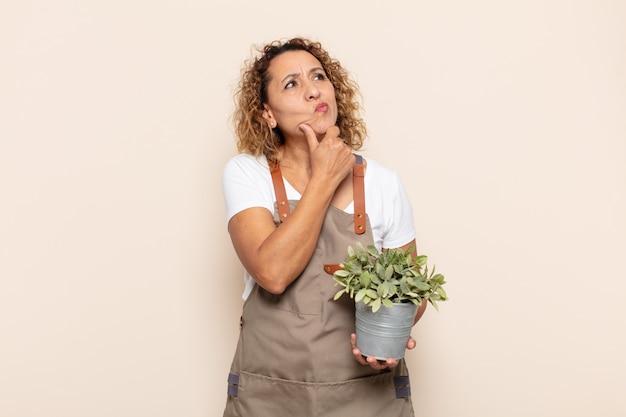 Латиноамериканская женщина среднего возраста думает, чувствует себя неуверенно и растерянно, с разными вариантами, задается вопросом, какое решение принять