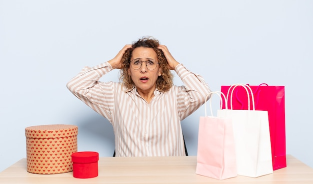 Hispanic middle aged woman feeling stressed, worried, anxious or scared, with hands on head, panicking at mistake