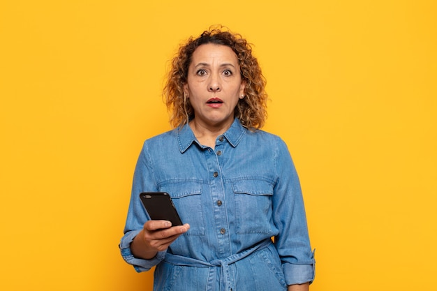 Латиноамериканка средних лет выглядит очень шокированной или удивленной, смотрит с открытым ртом и говорит: