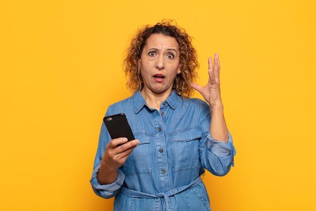 Латиноамериканка средних лет кричит с поднятыми руками, чувствуя ярость, разочарование, стресс и расстройство