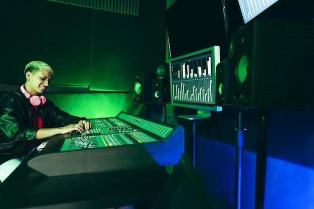 ヒスパニック系の音楽プロデューサーがブティックスタジオ内で新しい音楽アルバムをミックス-女性の手に主な焦点