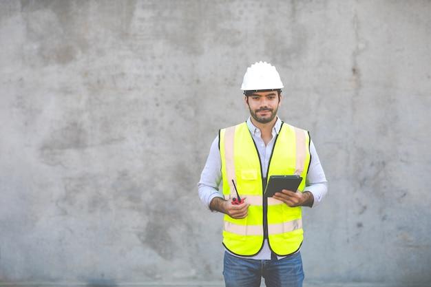 Испаноязычные или ближневосточные люди. портрет рабочего-строителя, держащего красный изолят радио и цифрового планшета на сером фоне цемента. инженер-проектировщик на строительной площадке.