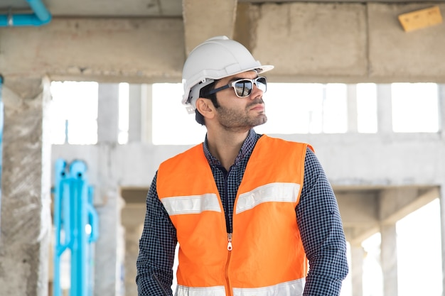 Испаноязычные или ближневосточные люди. портрет строителя на строительной площадке.
