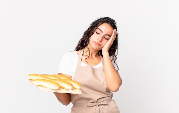 Латиноамериканка симпатичная женщина-повар чувствует скуку, разочарование и сонливость после утомительной и держащей тройку хлебных булочек