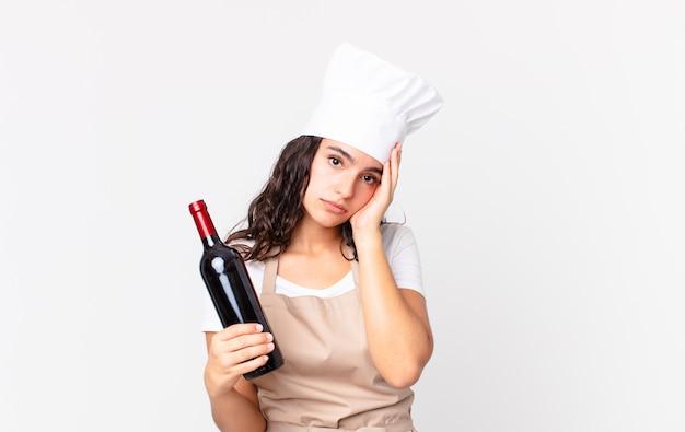 Латиноамериканская симпатичная женщина-повар чувствует скуку, разочарование и сонливость после утомительного и держащего бутылку вина