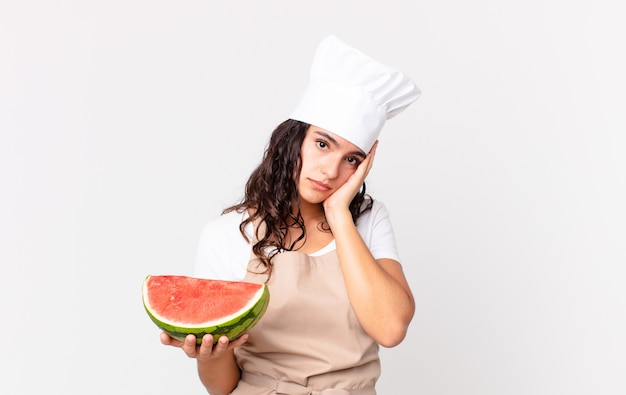 Hispanic pretty chef woman feeling bored, frustrated and sleepy after a tiresome and holding a watermelon