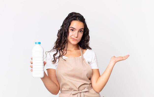 Латиноамериканка симпатичная женщина-повар чувствует себя озадаченной и сбитой с толку, сомневается и держит бутылку с молоком