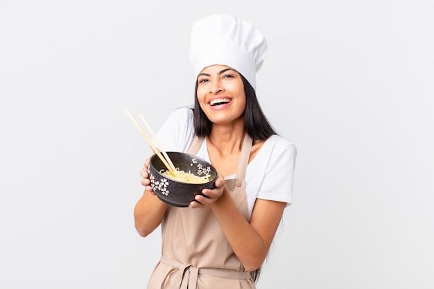 Hispanic pretty chef woman holding a noodles bowl