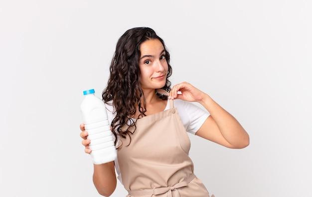 Латиноамериканская симпатичная женщина-повар, выглядящая высокомерной, успешной, позитивной и гордой, держит бутылку молока