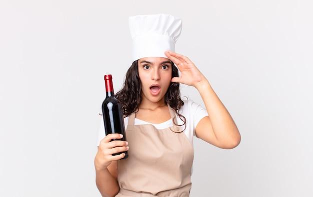 Латиноамериканская симпатичная женщина-повар выглядит счастливой, удивленной и удивленной и держит бутылку вина