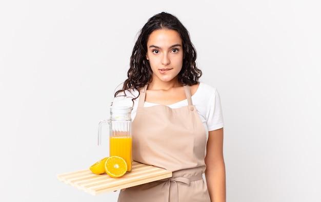 困惑して混乱しているように見え、オレンジジュースを持っているヒスパニック系のかわいいシェフの女性