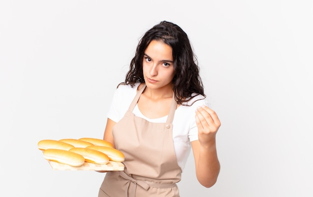 Hispanic pretty chef woman making capice or money gesture, telling you to pay and holding a bread buns troy