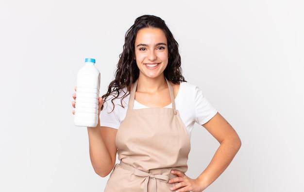 Испаноязычная красивая женщина-повар счастливо улыбается, положив руку на бедро и уверенно, и держит бутылку с молоком