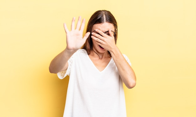 Hispanic pretty woman covering face with hand and putting other hand up front to stop camera, refusing photos or pictures