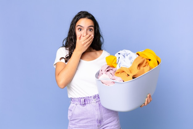 Hispanic pretty woman covering mouth with hands with a shocked and holding a washing clothes basket