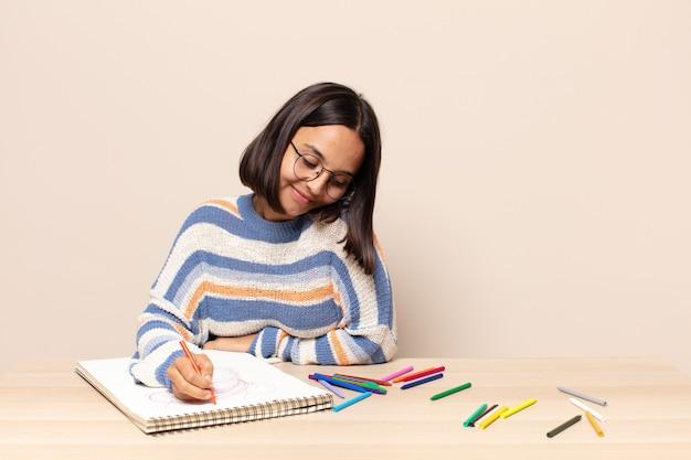 Hispanic pretty woman drawing on a sketch book
