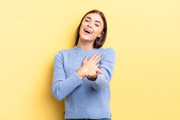 Латиноамериканская симпатичная женщина чувствует себя счастливой и влюбленной, улыбаясь, прижав одну руку к сердцу, а другую протянув вперед