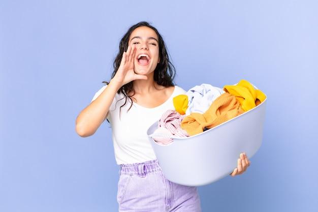 Латиноамериканская симпатичная женщина чувствует себя счастливой, громко кричит, прижав руки ко рту и держа корзину для стирки белья